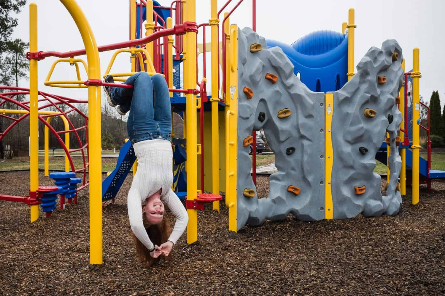 Shannon McAlister, director of the John 3:16 center in Littleton, North Carolina, hangs off the monkey bars on the facility's playground. Photo by Shawn Poynter