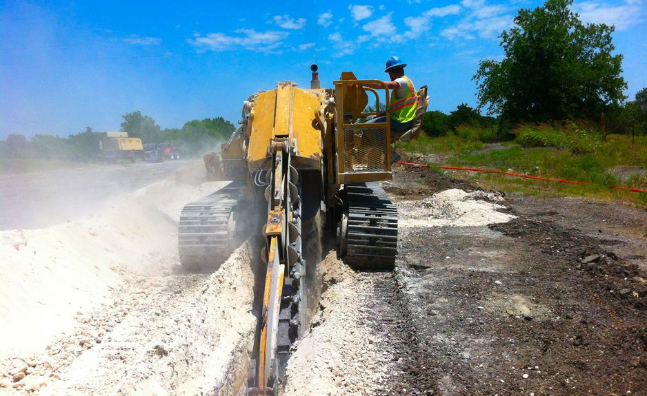 A trencher cuts a ditch for fiber lines between Ardmore and Madill, Oklahoma.