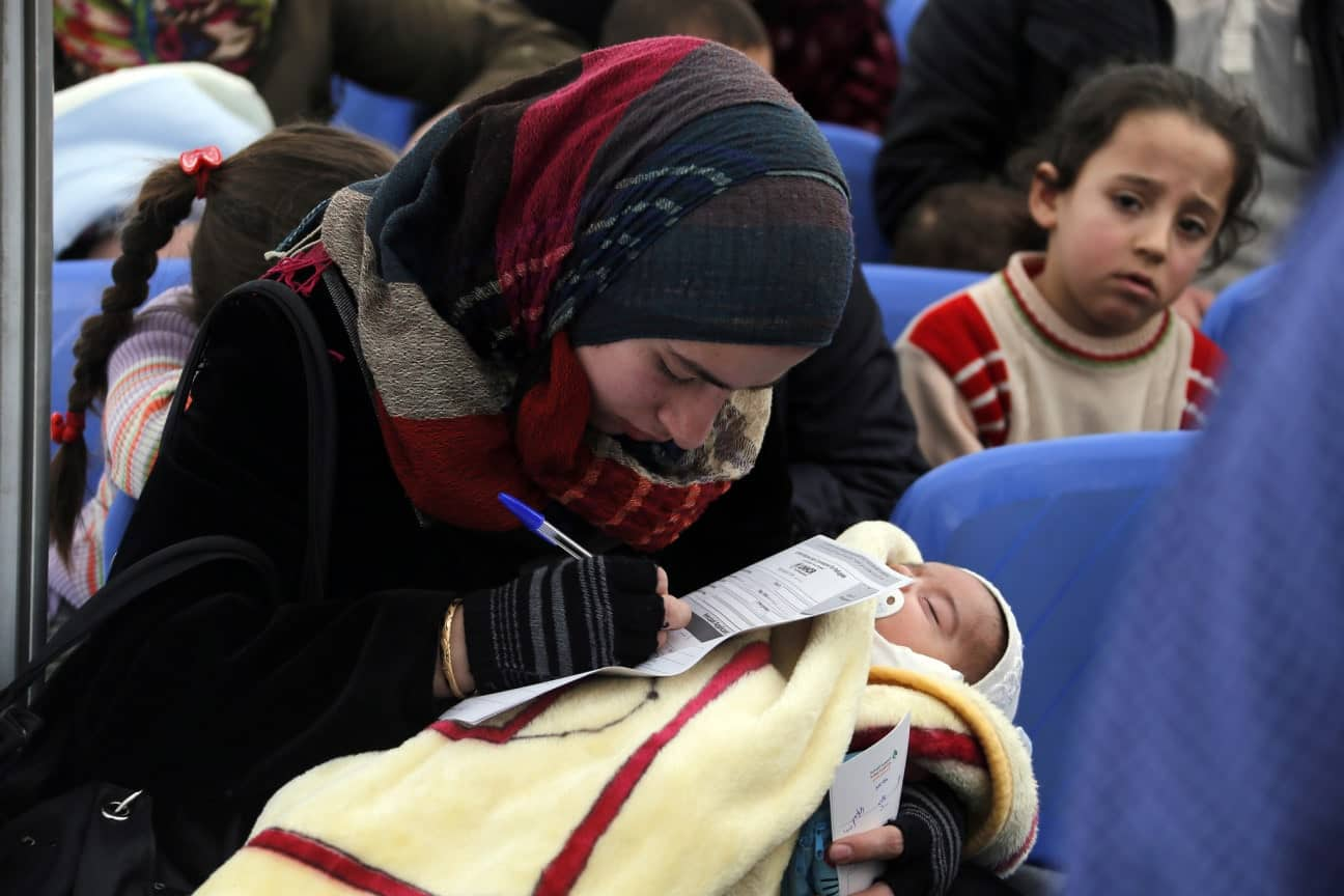 Yearning to breathe  free: A refugee holds her infant and fills out an application at a United Nations refugee center in Lebanon in 2014. (World Bank Photo Collection)