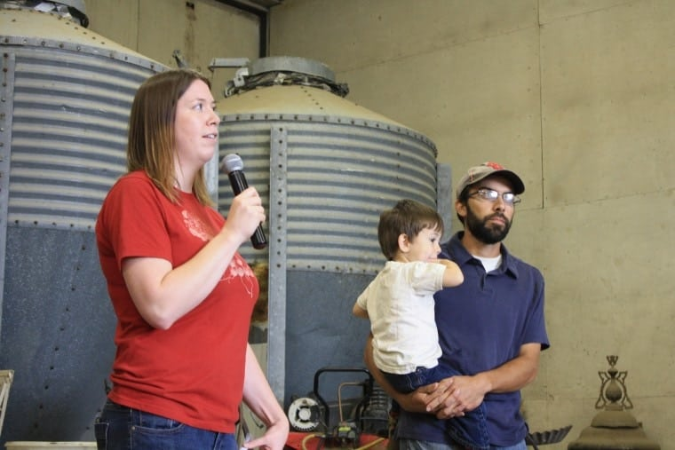 Ellen Walsh-Rosmann tells the audiences about her and Daniel's latest local food supply projects, while Daniel holds their son Xavier. Photo via Practicalfarmers.com