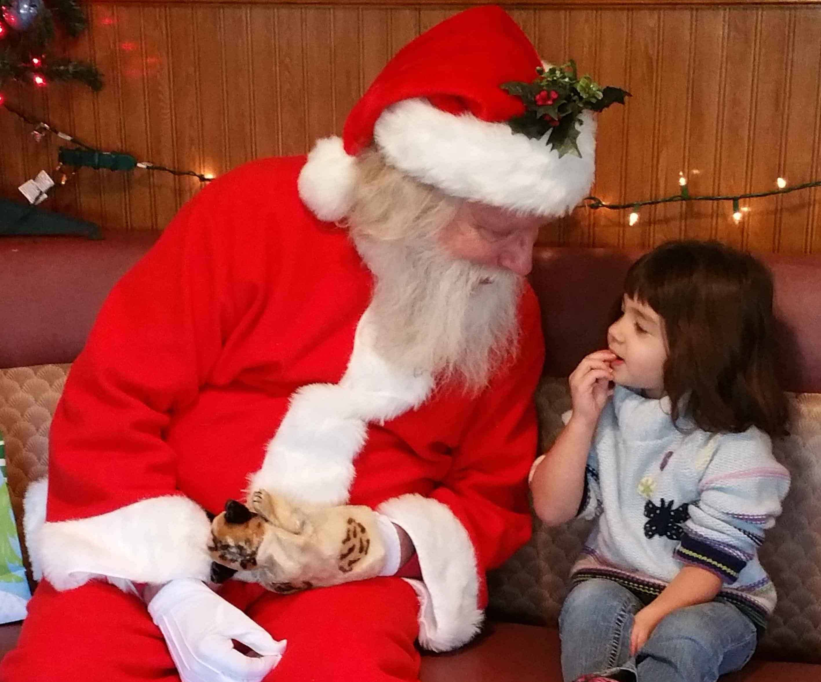 A child pauses to choose her words carefully while talking to Santa at the Highway Family Restaurant in Bushnell. (Photo by Shannon L. Price)