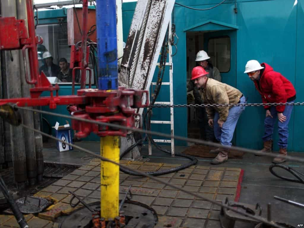 Floor hands and engineers adjust a down-hole motor used for directional drilling on a gas-drilling platform in the Barnett Shale near Fort Worth, Texas.
