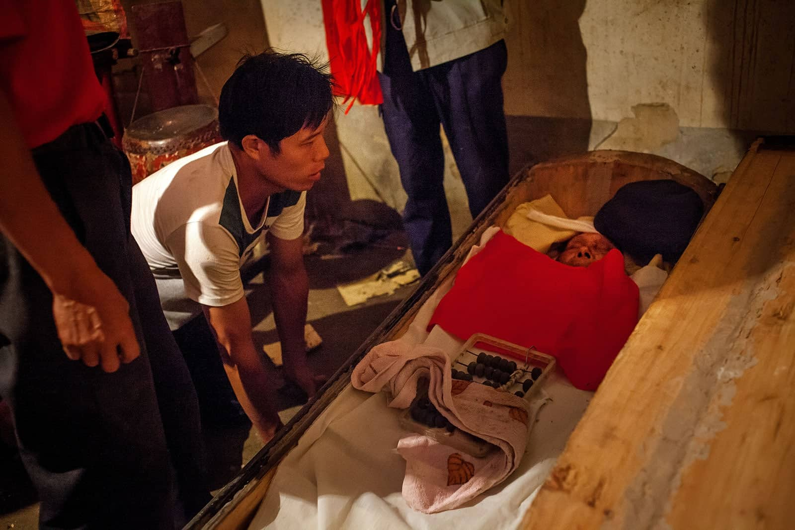 The Huang's second eldest son, Huang Shou-Bin, kneels at his father's coffin to say goodbye one last time.