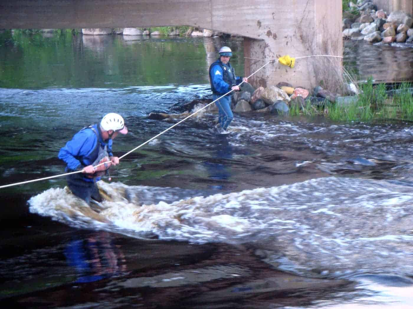The author's husband, center, helps set up a stream crossing exercise during a fire department river rescue training.