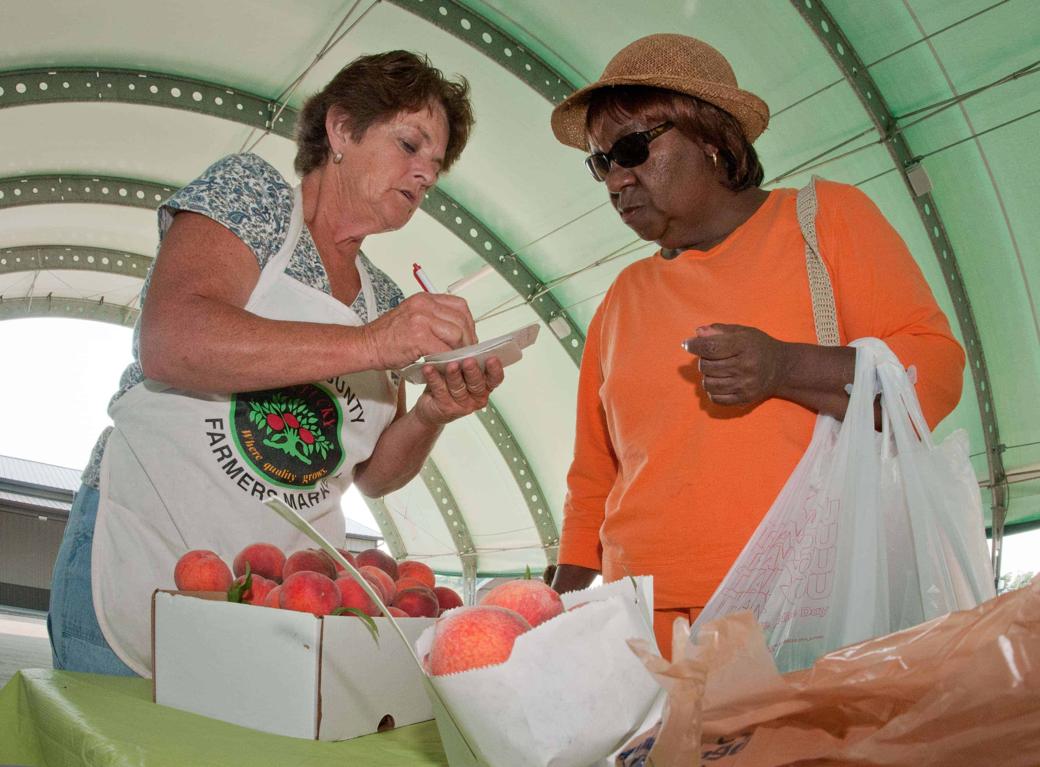 """""""The Peach Lady"""" (left) is happy to share a peach pie recipe with a customer Bath County Agricultural Education and Marketing Center, Owingsville, Kentucky. The USDA Rural Development grant program that supported the center is now one of the programs included in an initiative to encourage regional cooperation. Photo by Lance Cheung/USDA"""
