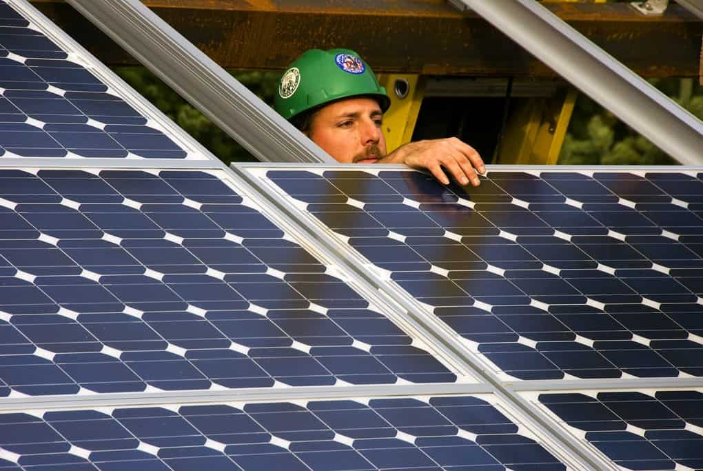 A worker installs solar panels in Oregon in 2010.  States need to ensure that new jobs created by reducing CO2 emissions help people in coal-dependent communities, according to a report from the Institute for Agriculture and Trade Policy. (Oregon Dept. of Transportation via Flickr)