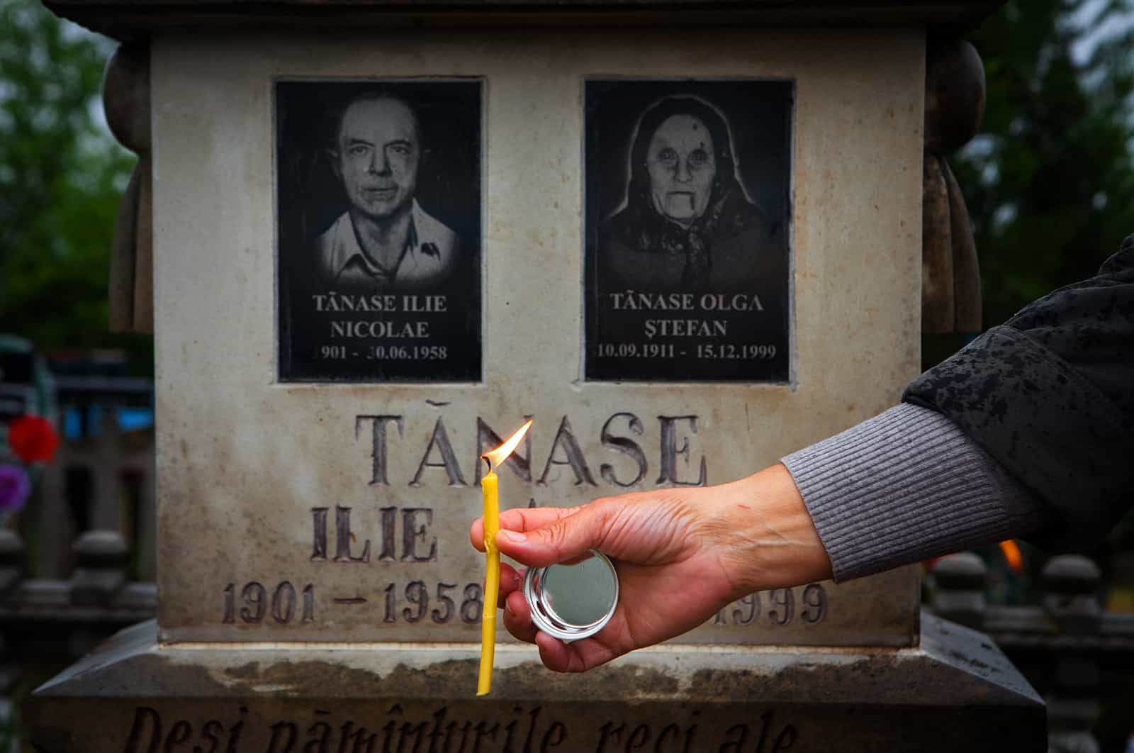 Nina Postica puts a candle in the earth in front of her parents' grave in Moldova. Photos by Clary Estes.