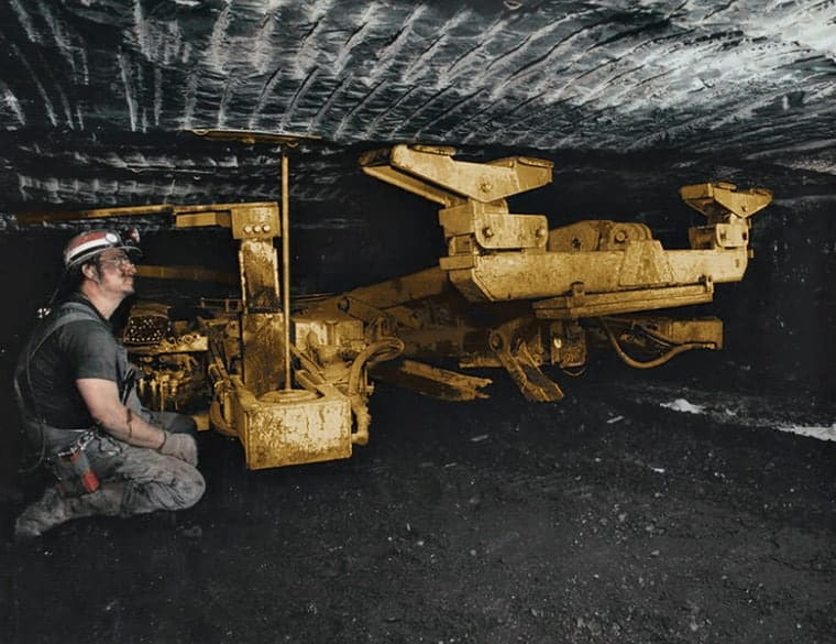A miner operates a roof bolter, securing the top to prevent collapse. (Photo: Advanced Mining Solutions)