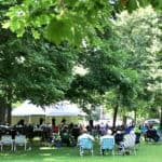 The audience gathers in the shade to listen to performers at the 2016 Bishop Hill Folk Festival in western Illinois. The July event is part of a range of activities at the historic village -- formed by Swedish utopians in the 1840s (Photo courtesy of Bishop Hill Heritage Association)