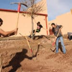 Caleb Weaver of Borderlands Restoration  works with Patagonia Union High School students in Santa Cruz, Arizona, to dig terraces before installing pollinator plants at the school's pollinator garden.