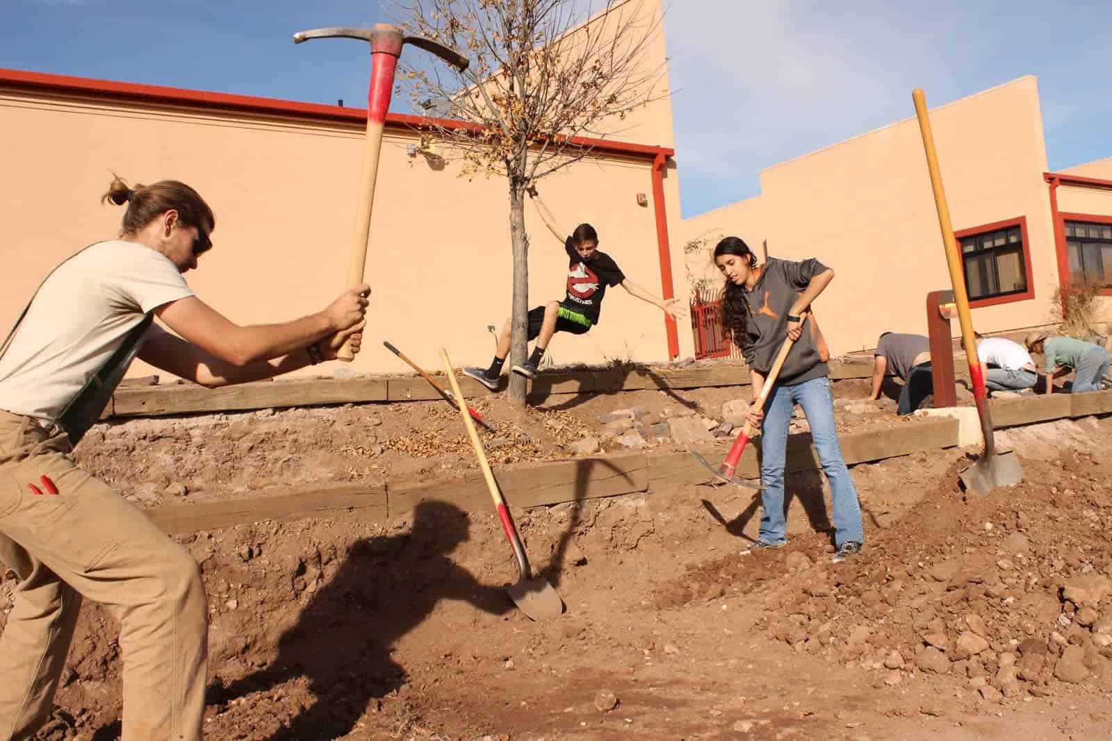 Caleb Weaver of Borderlands Restoration  works with Patagonia Union High School students in Santa Cruz, Arizona, to dig terraces before installing pollinator plants at the school's pollinator garden.