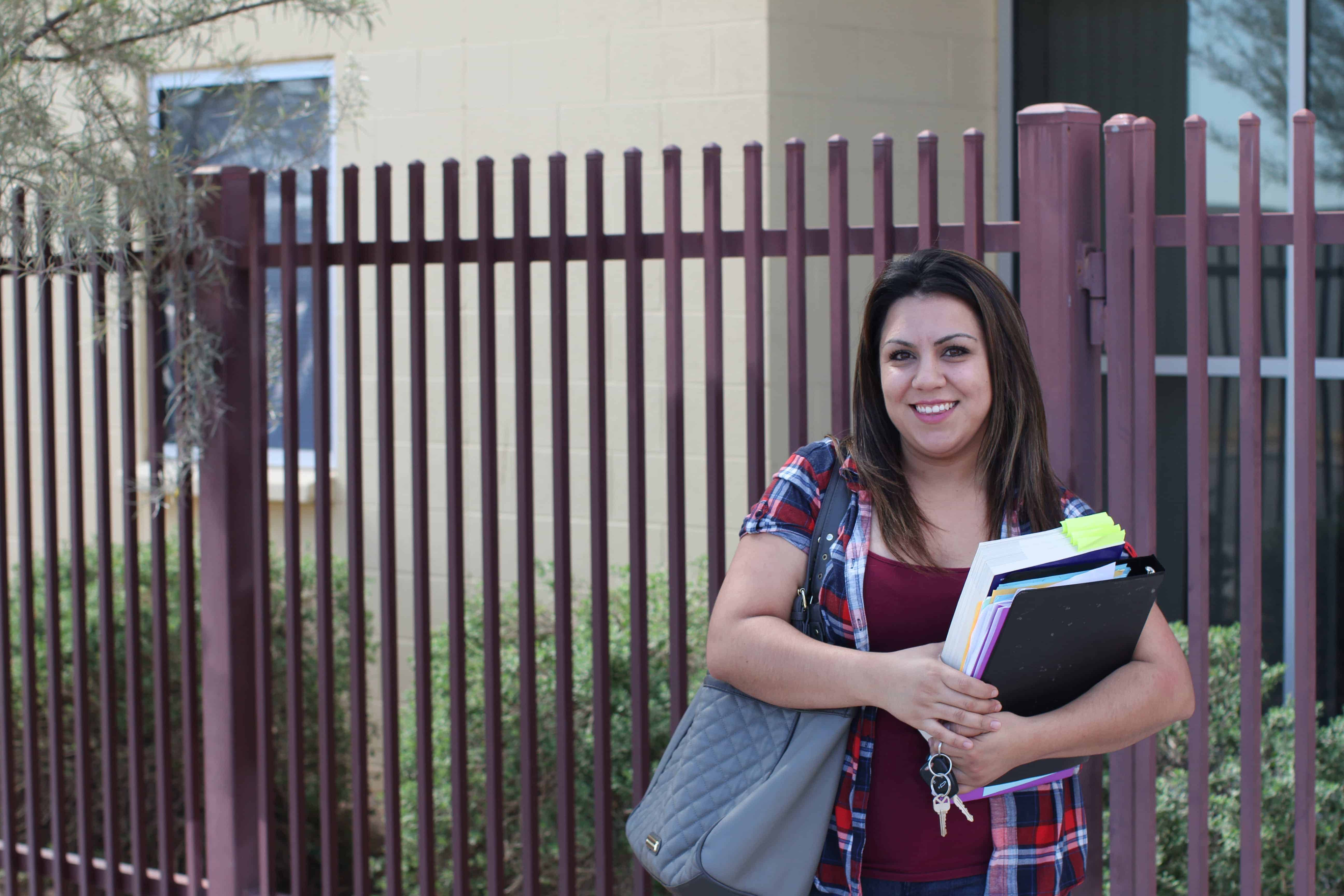 Zahide Betancourt holds her textbooks in front of Wilson Community Center in Phoenix, where she takes a GED prep course. Photo by Cassie Ronda/PIN Bureau