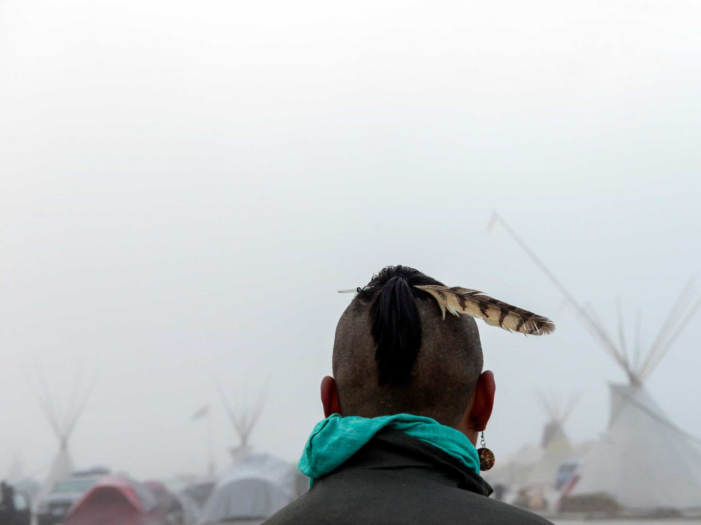A man from the Muskogee tribe looks at the Oceti Sakowin shrouded in mist during a protest against the Dakota Access pipeline near the Standing Rock Indian Reservation near Cannon Ball, North Dakota, Photo by Stephanie Keith/Reuters