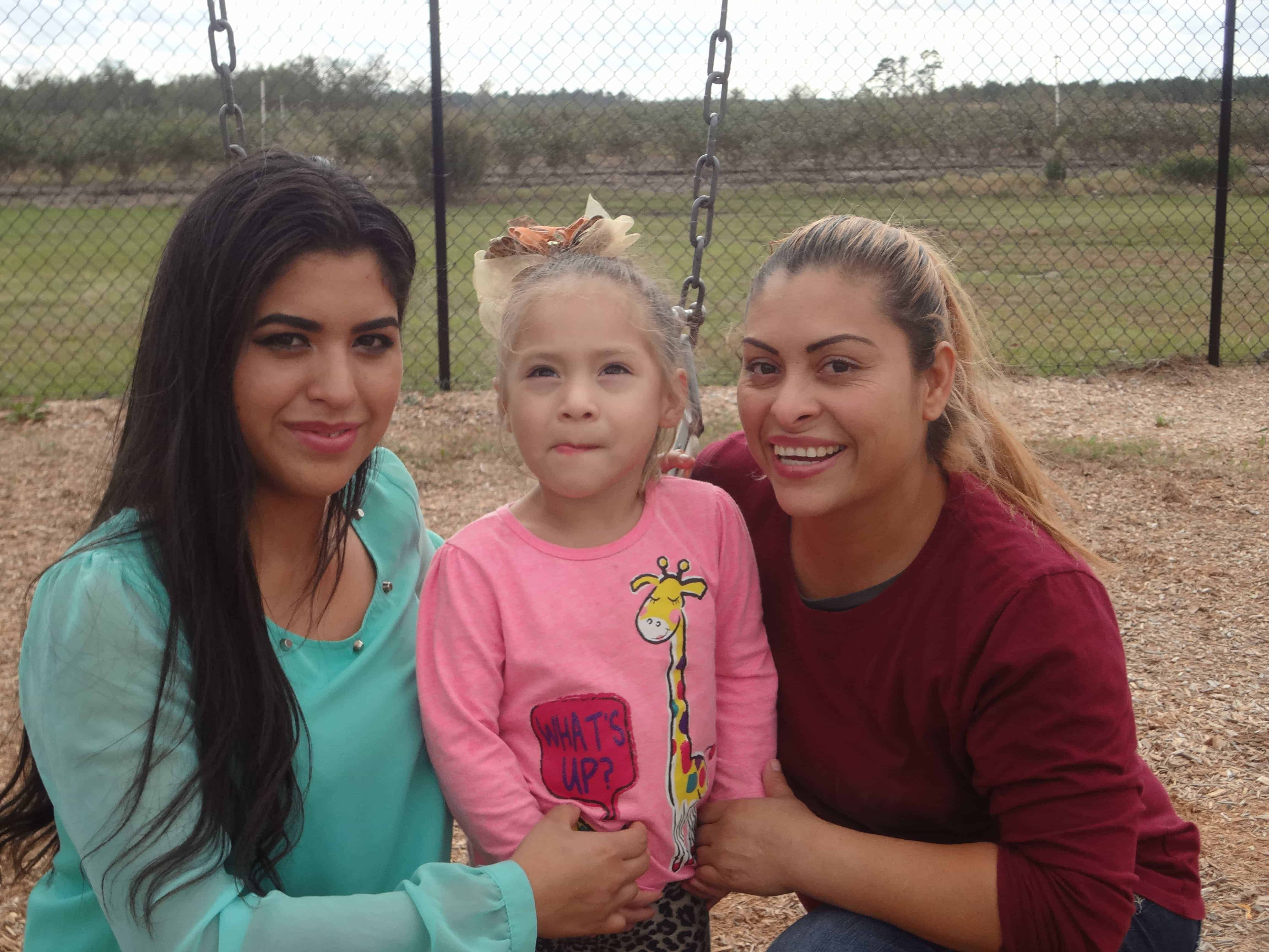 Eva Gonzalez, 3, flanked by her sister Alondra Martinez (left) and mom, Nelly Gonzalez, attends preschool at the East Coast Migrant Head Start Project center in Faison, North Carolina.