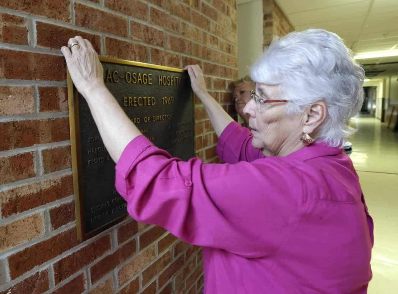 A hospital worker removing a plaque from Sac-Osage Hospital, which closed its doors in 2015. Photo by Orlin Wagner/AP