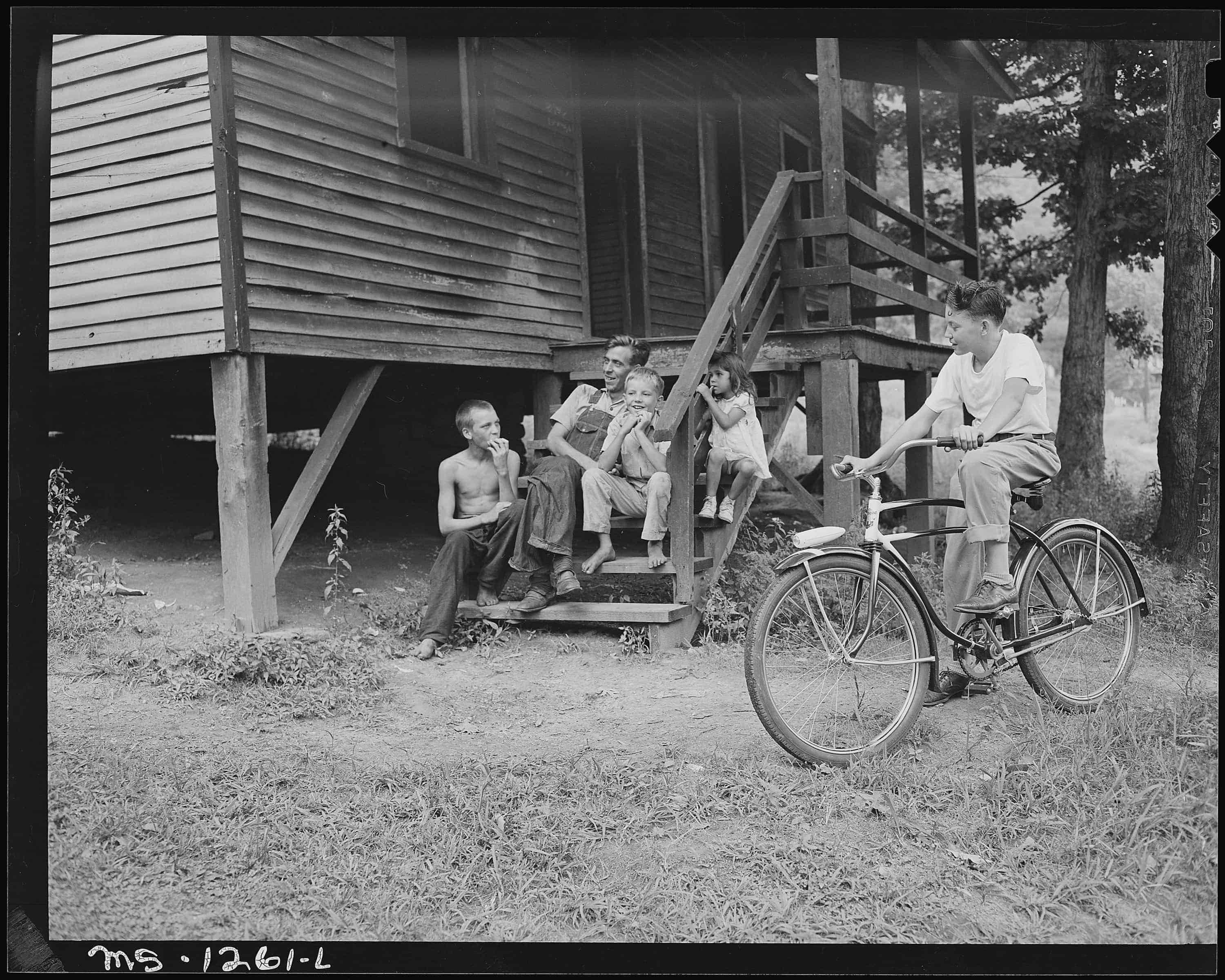A_miner_and_children_on_steps_of_a_typical_house._Kingston_Pocahontas_Coal_Company,_Exeter_Mine,_Big_Sandy_Housing…_-_NARA_-_540760