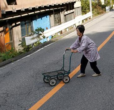 A local resident walks across a street in Nanmoku Village